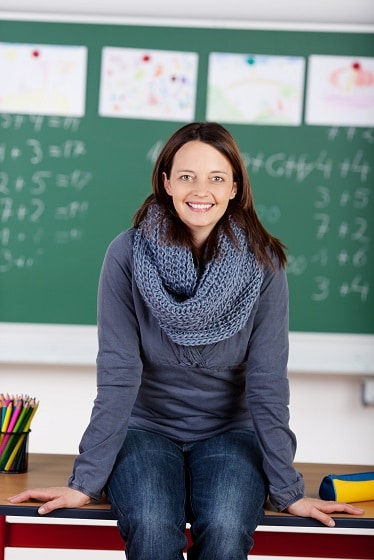 Happy teacher sitting on the table in front of blackboard
